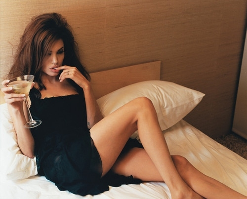 angelina jolie, bed, brunette, cocktail, dress, drink, fashion, gal, girl, hair, legs, little black dress, messy hair, pillows, sexy